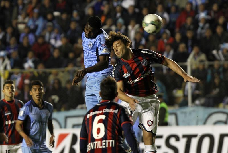 El jugador Carlos Tenorio (c-i) de Bolívar ante Fabricio Fontanini (d) de San Lorenzo. EFE