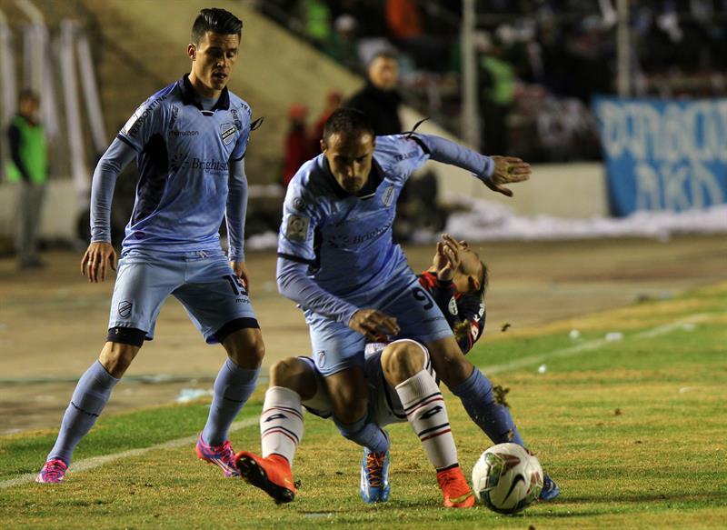 El jugador José Luis Sánchez Capdevila de Bolívar de Bolivia (frente) disputa el balón con Héctor Villalba (atrás) de San Lorenzo de Argentina. EFE