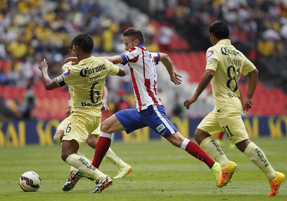 El jugador del Atlético de Madrid Saúl Ñíguez (c) disputa el balón con Juan Carlos Valenzuela (i) de América. Foto: EFE
