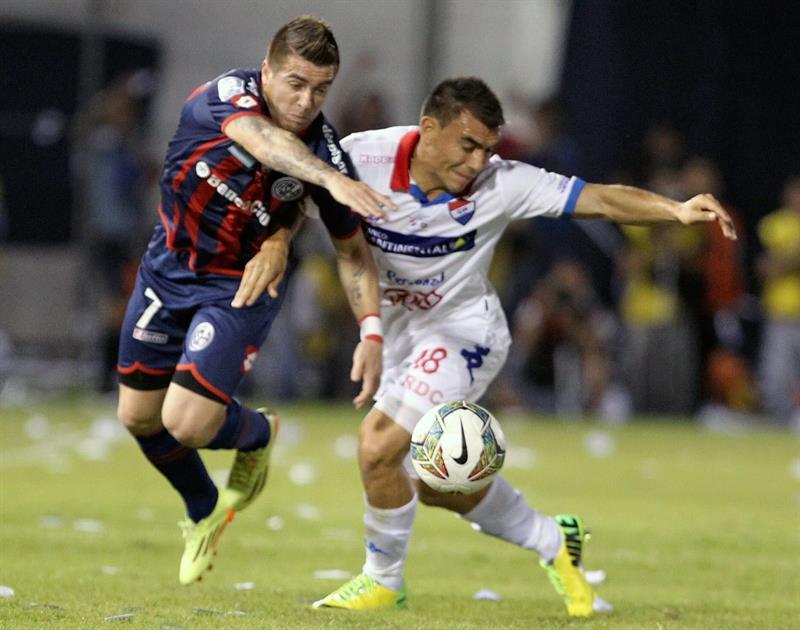 El jugador de San Lorenzo Julio Buffarini (i) disputa el balón con Derlis Orué (d), de Nacional. Foto: EFE