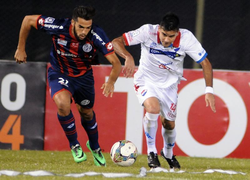 El jugador de San Lorenzo Juan Mercier (i) disputa el balón con David Mendoza (d) de Nacional. Foto: EFE