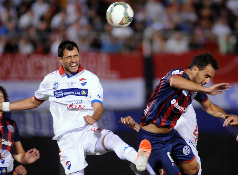 El jugador de San Lorenzo Gabriel Esparza (d) disputa el balón con Marcos Riveros (i) de Nacional. Foto: EFE