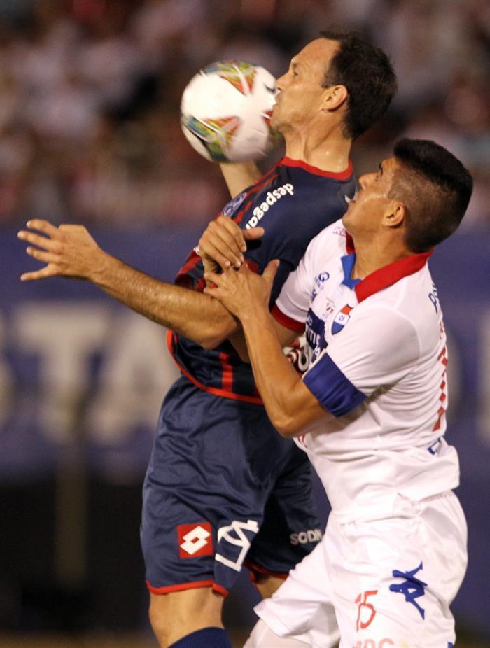 El jugador de San Lorenzo Mauro Mats (i) disputa el balón con Raúl Píris (d) de Nacional. Foto: EFE