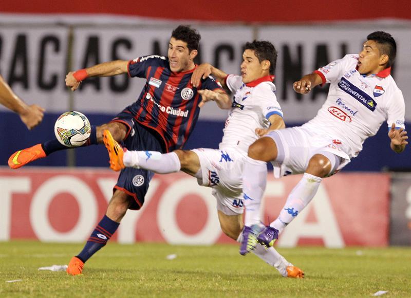 El jugador de San Lorenzo Mauro Matos (i) patea el balón ante la marca de Silvio Torales (c) y Raúl Píris (d), de Nacional. Foto: EFE