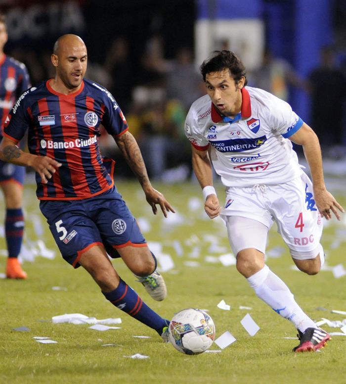El jugador de San Lorenzo Emmanuel Mas (i) disputa el balón con Marcos Melgarejo (d) de Nacional. Foto: EFE