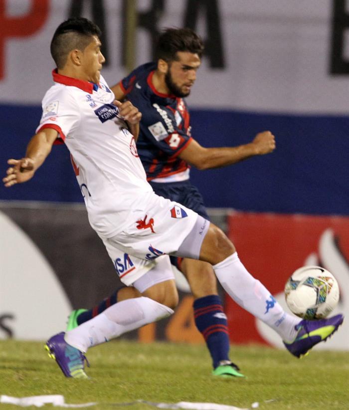 El jugador de San Lorenzo Julio Buffarini (frente) disputa el balón con Julián Benítez (atrás) de Nacional. Foto: EFE