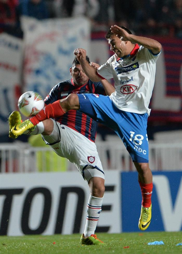 El jugador de San Lorenzo Néstor Ortigoza (i) disputa el balón con Derlis Orué (d), de Nacional. Foto: EFE