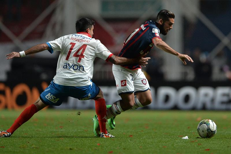 El jugador de San Lorenzo Emmanuel Mas (d) supera la marca de Marcos Melgarejo (i), de Nacional. Foto: EFE