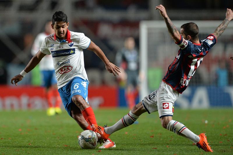 El jugador de San Lorenzo Leandro Romagnoli (d) disputa el balón con Silvio Torales (i), de Nacional. Foto: EFE