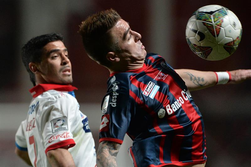 El jugador de San Lorenzo Julio Buffarini (d) recibe el balón ante la marca de Julián Benítez (i), de Nacional. Foto: EFE