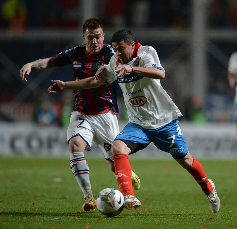 El jugador de San Lorenzo Julio Buffarini (d) marca a Julián Benítez (d), de Nacional. Foto: EFE