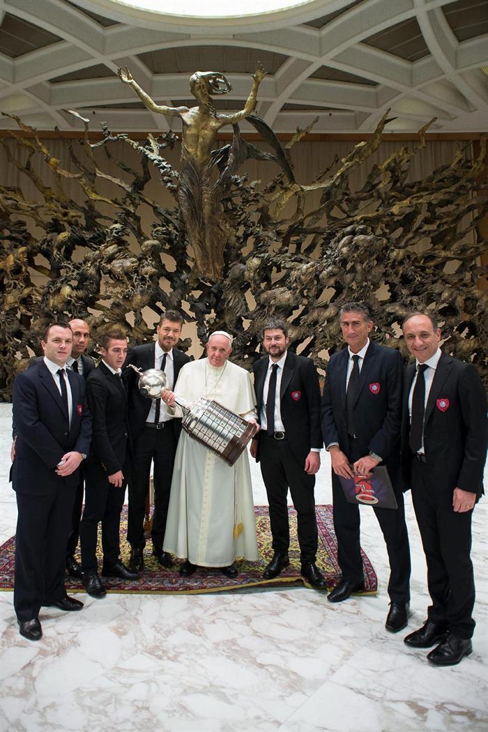 Fotografía facilitada por el Observador Romano que muestra al papa Francisco (c), sujetando la Copa Libertadores, rodeado de miembros del San Lorenzo. EFE