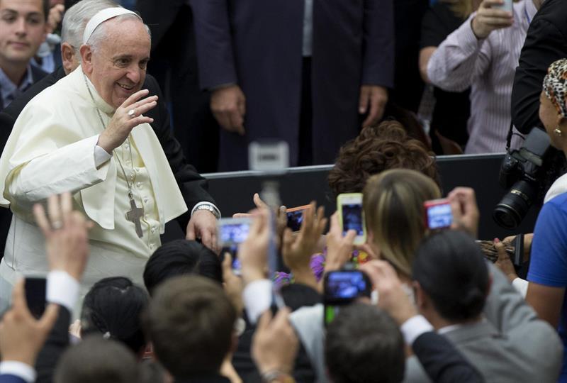 El Papa Francisco saluda a sus seguidores que le fotografían antes de comenzar la audiencia pública de los miércoles en el Aula Nervi (Vaticano). EFE