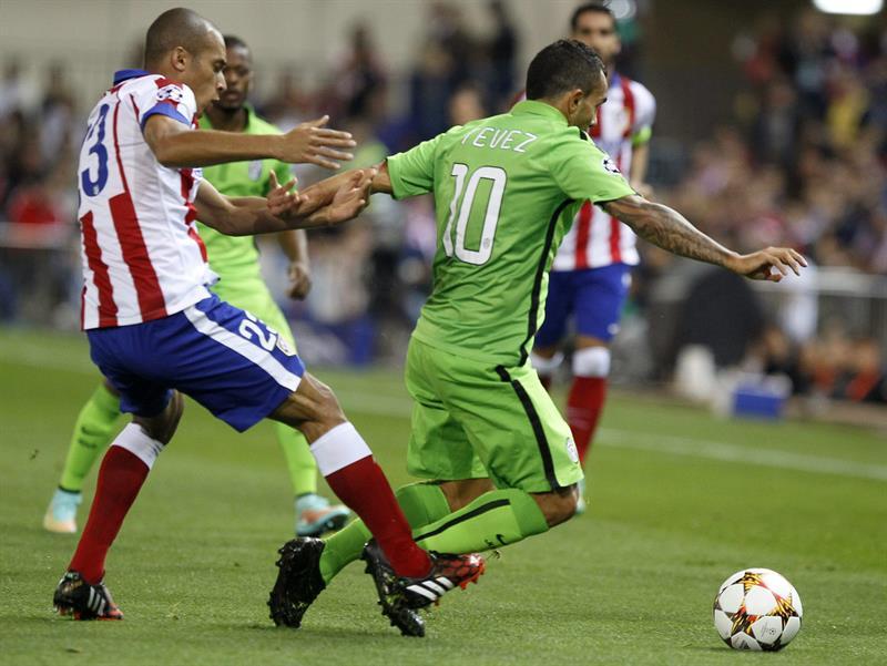 El defensa brasileño del Atlético de Madrid Joao Miranda (i) lucha el balón con el argentino Carlos Tévez, de la Juventus. EFE