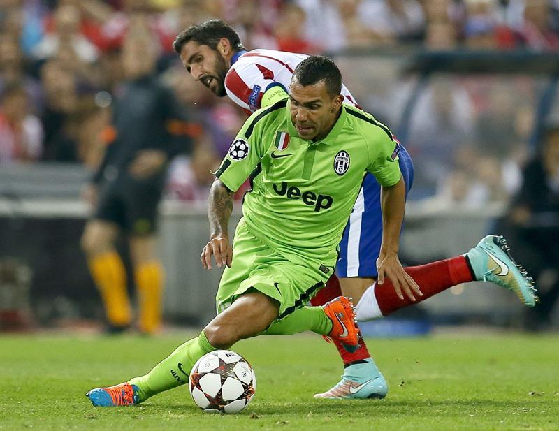 El delantero argentino del Juventus Carlos Tévez (d) con el balón ante el centrocampista del Atlético de Madrid Raúl García. EFE