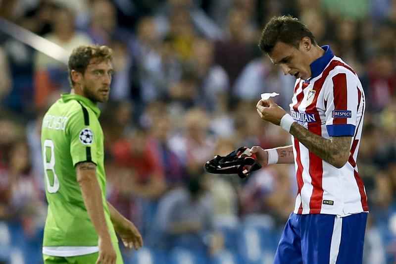 El delantero croata del Atlético de Madrid Mario Mandzukic (d) se quita el protector nasal durante el partido de la segunda jornada de la fase de grupos de la Liga de Campeones. EFE