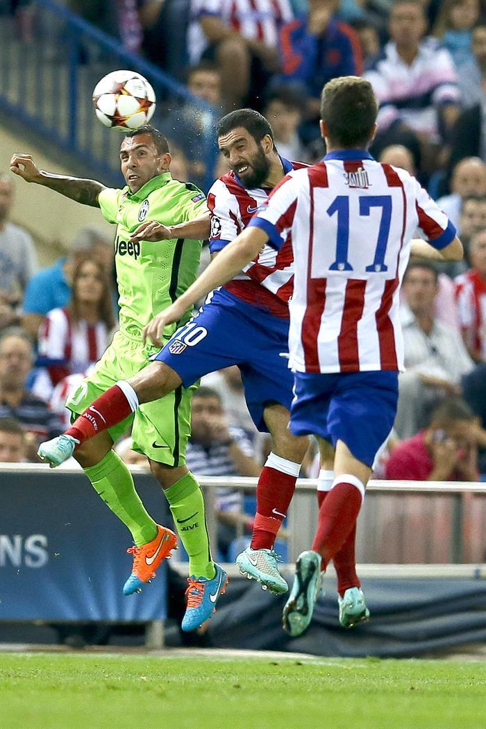 El centrocampista turco del Atlético de Madrid Arda Turan (c) salta por el balón con el argentino Carlos Tévez (i), de la Juventus. EFE