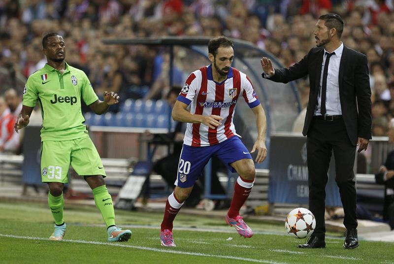 El defensa del Atlético de Madrid Juanfran Torres (d) recibe instrucciones de su entrenador, el argentino Diego Simeone (d), ante el defensa francés del Juventus Patricie Evra. EFE
