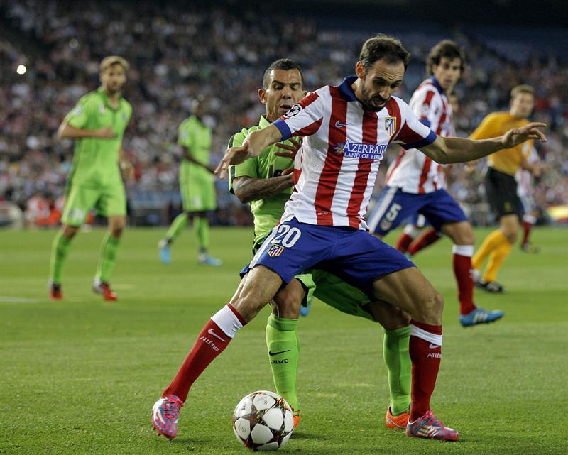 El defensa del Atlético de Madrid Juanfran (delante) lucha el balón con el argentino Carlos Tévez, de la Juventus. EFE
