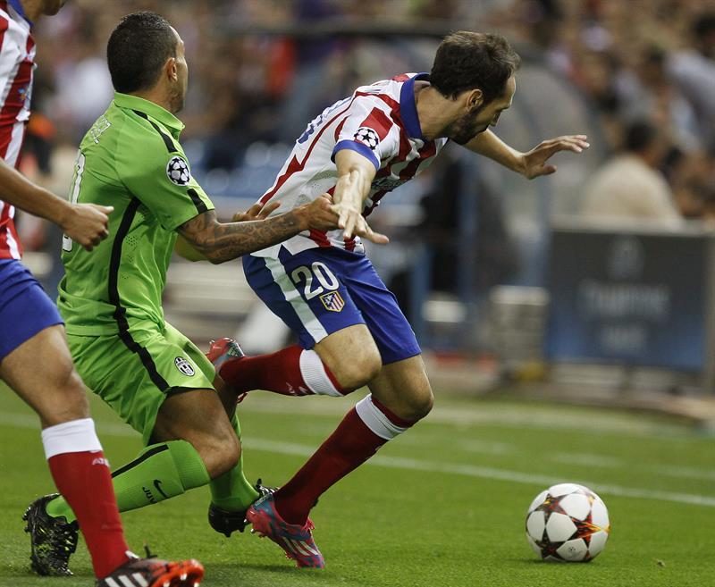 El defensa del Atlético de Madrid Juanfran (d) lucha el balón con el argentino Carlos Tévez, de la Juventus. EFE