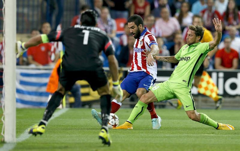 El centrocampista turco del Atlético de Madrid Arda Turan (c) con el balón ante el centrocampista del Juventus Claudio Marchisio (d) y el portero Gianluigi Buffon. EFE