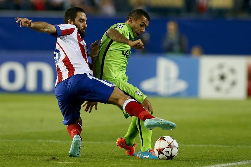 El centrocampista turco del Atlético de Madrid Arda Turan (i) lucha el balón con el argentino Carlos Tévez, de la Juventus. EFE