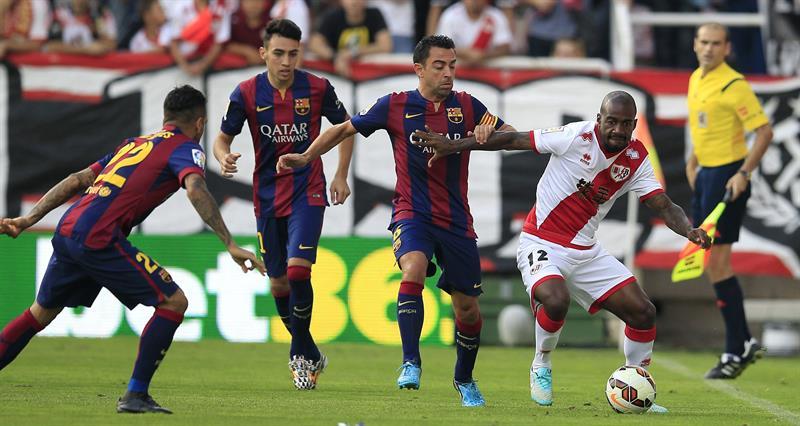 El delantero francés del Rayo Vallecano Gaël Kakuta (d) pelea un balón con los jugadores del Barcelona Xavi Hernández. Foto: EFE