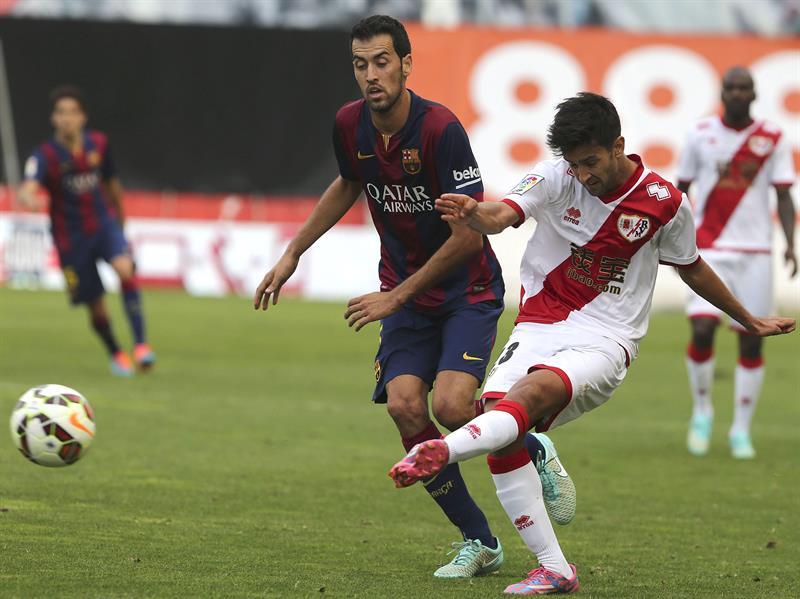 El centrocampista del Barcelona Sergio Busquets (i) pelea un balón con el centrocampista del Rayo Vallecano Alberto Bueno. Foto: EFE