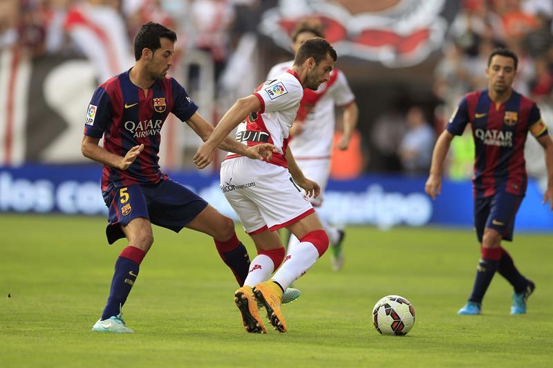 El delantero brasileño del Rayo Vallecano Leo Baptistao (d) pelea un balón con el centrocampista del Barcelona Sergio Busquets. Foto: EFE