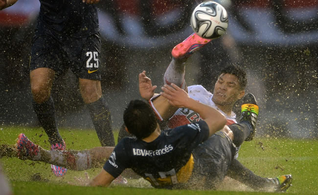 Teófilo Gutíerrez (atrás) del River Plate disputa el balón con Marcelo Meli de Boca Juniors. EFE