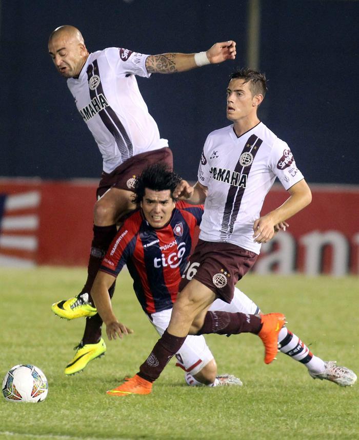 El jugador de Cerro Porteño Fidencio Oviedo (c) cae mientras disputa el balón con Lucas Melano (d) y Santiago Silva (i), de Lanús. Foto: EFE