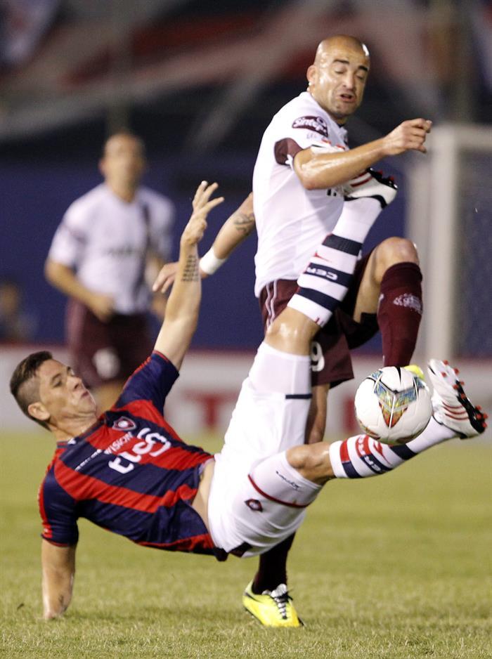 El jugador del Cerro Porteño de Paraguay Danilo Ortiz (abajo) disputa el balón con Santiago Silva (d) de Lanús de Argentina. Foto: EFE