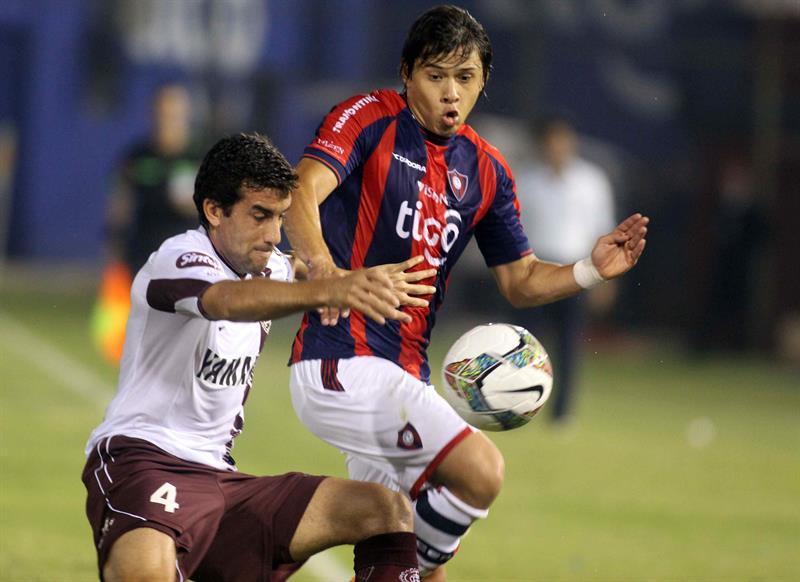 El jugador de Cerro Porteño Óscar Romero disputa el balón con Carlos Araujo (i), de Lanús. Foto: EFE
