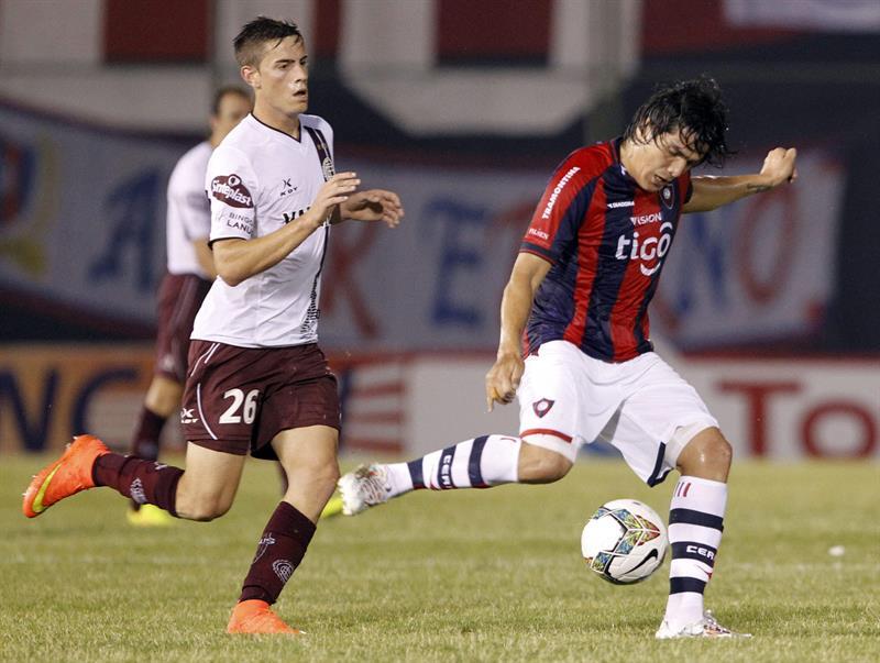 El jugador del Cerro Porteño de Paraguay Fidencio Oviedo (d) disputa el balón con Lucas Melano (i) de Lanús de Argentina. Foto: EFE
