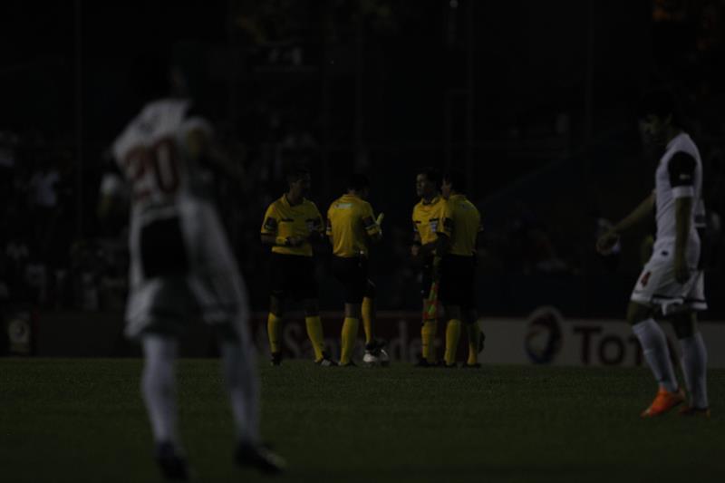 Fotografía de los árbitros y jugadores durante un apagón durante el partido entre el Libertad de Paraguay y River Plate de Argentina. Foto: EFE