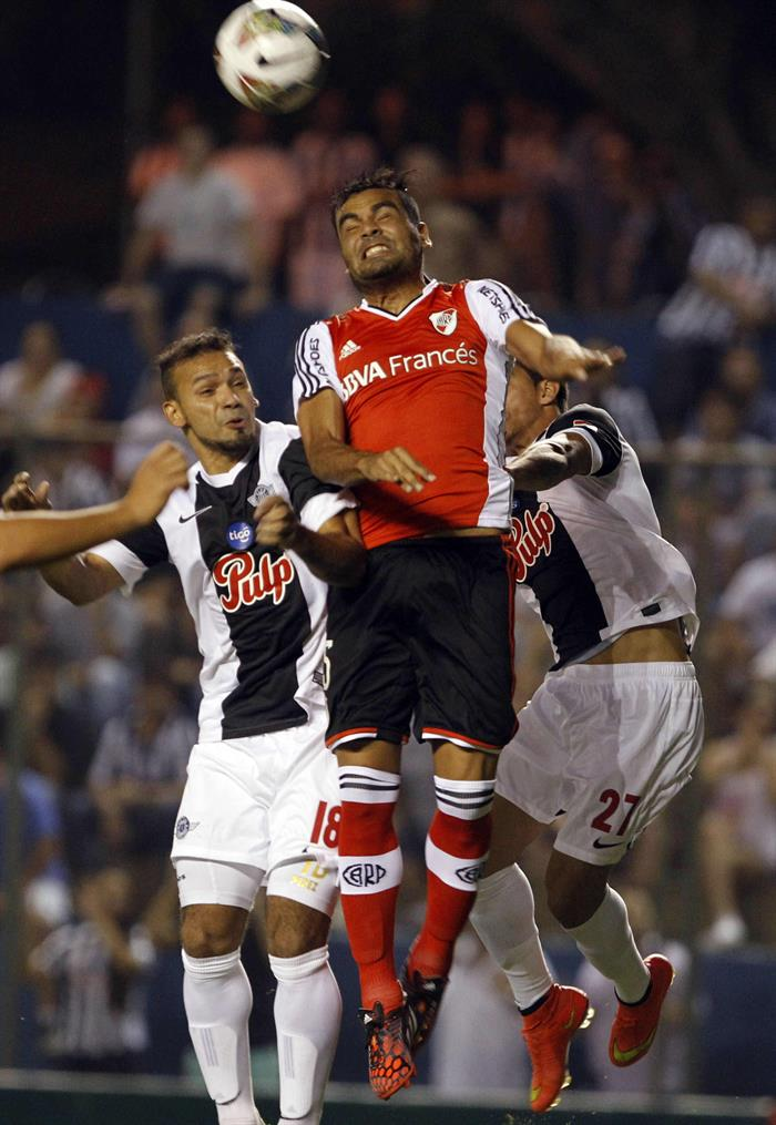 Los jugadores de Libertad de Paraguay Dionicio Pérez (i) y Jorge Daniel González (d) pelean el balón con Gastón Hernán Oliveira (c) del River Plate de Argentina. Foto: EFE