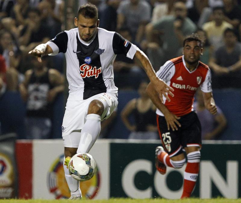 El jugador de Libertad de Paraguay Dionicio Pérez (i) pelea el balón con Gastón Hernán Oliveira (d) del River Plate de Argentina. Foto: EFE