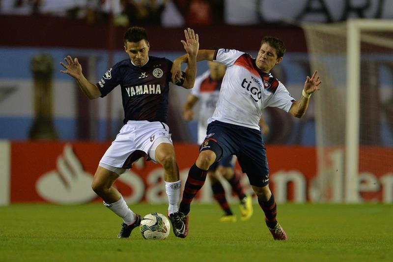 Mauricio Sperdutti (d) de Cerro Porteño de Paraguay disputa el balón con Maximiliano Velázquez (i) de Lanús. Foto: EFE