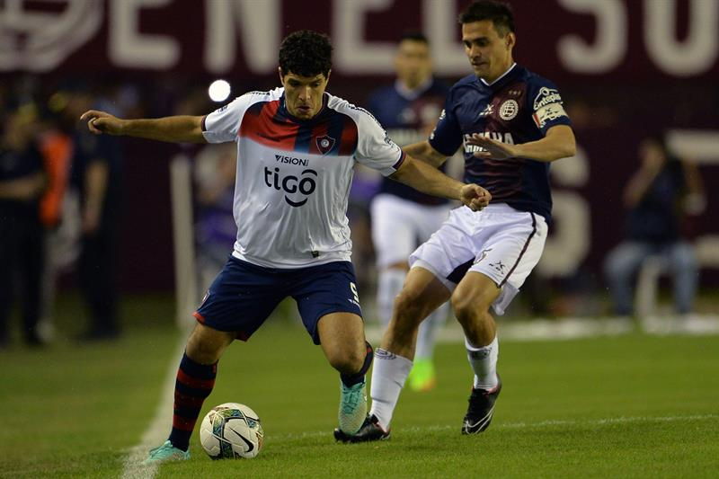 José Ortigoza (i) de Cerro Porteño de Paraguay disputa el balón con Maximiliano Velázquez (d) de Lanús. Foto: EFE