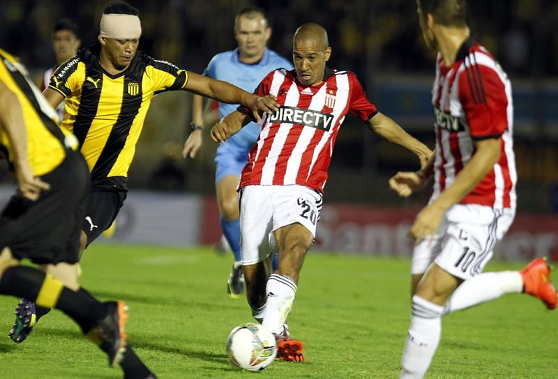 El jugador de Estudiantes de la Plata Diego Vera (c) disputa el balón con Sebastián Píriz (i) de Peñarol. Foto: EFE