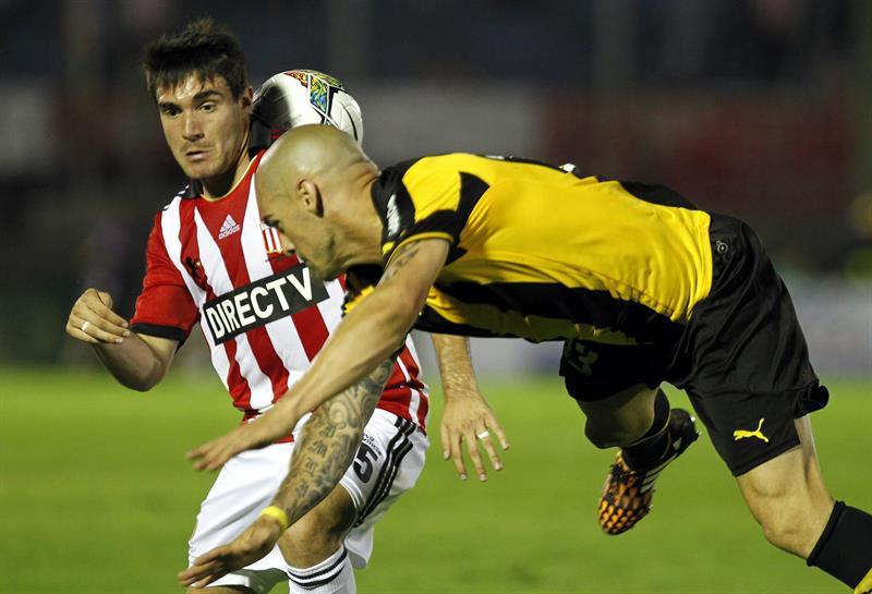 El jugador de Estudiantes de la Plata Ezequiel Cerutti (i) disputa el balón con Damián Macaluso (d) de Peñarol. Foto: EFE