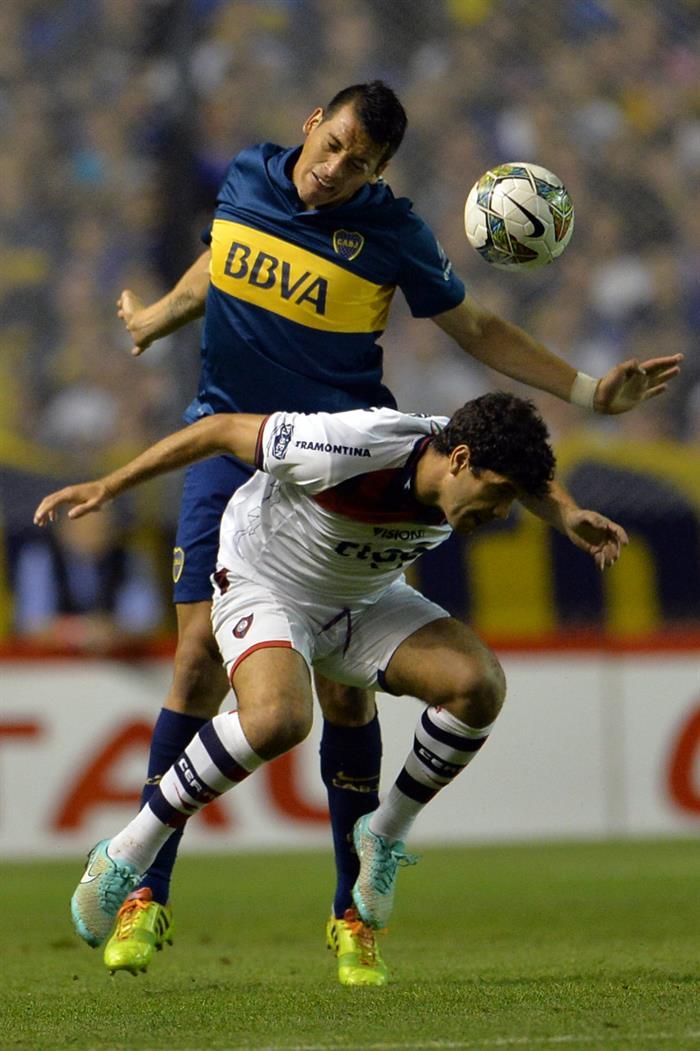 El jugador de Boca Juniors Claudio Pérez (arriba) disputa el balón con José Ortigoza (abajo), de Cerro Porteño. Foto: EFE