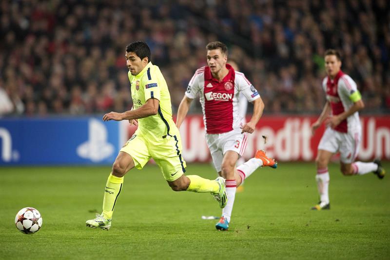 Luis Suárez (i), delantero uruguayo del FC Barcelona, controla el balón ante Joel Veltman (c), del Ajax de Ámsterdam. EFE