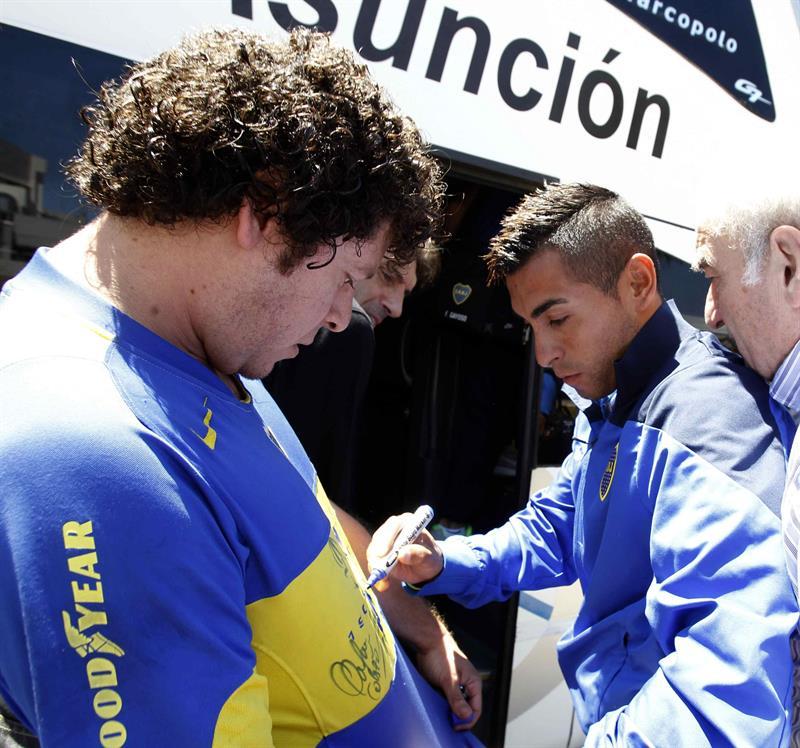 El jugador del equipo argentino Boca Juniors Federico Carrizo (d) firma autógrafos a su llegada a Asunción (Paraguay). Foto: EFE