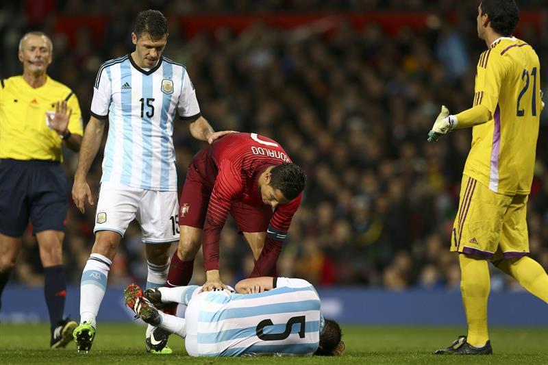 El jugador de Portugal Cristiano Ronaldo (c) habla con el jugador Lucas Biglia (abajo) de Argentina. Foto: EFE