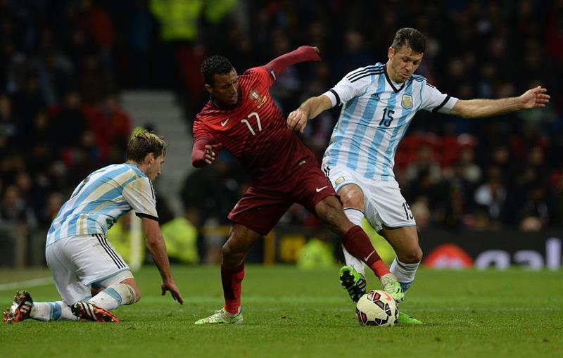 El jugador de Argentina Martin Dimichelis (d) disputa el balón con Nani (i) de Portugal. Foto: EFE