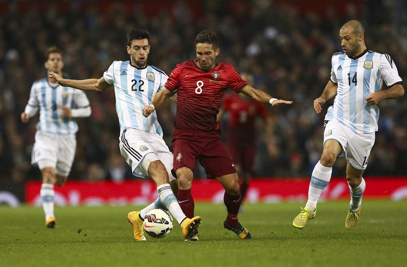 El jugador de Portugal Joao Moutinho (c) disputa un balón con Javier Pastore (i) y Javier Mascherano de Argentina. Foto: EFE