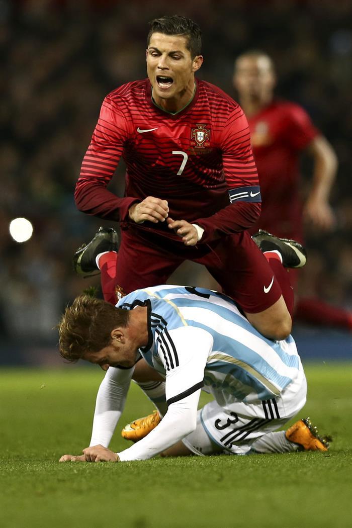El jugador de Portugal Cristiano Ronaldo (arriba) disputa el balón con Cristian Ansaldi. Foto: EFE