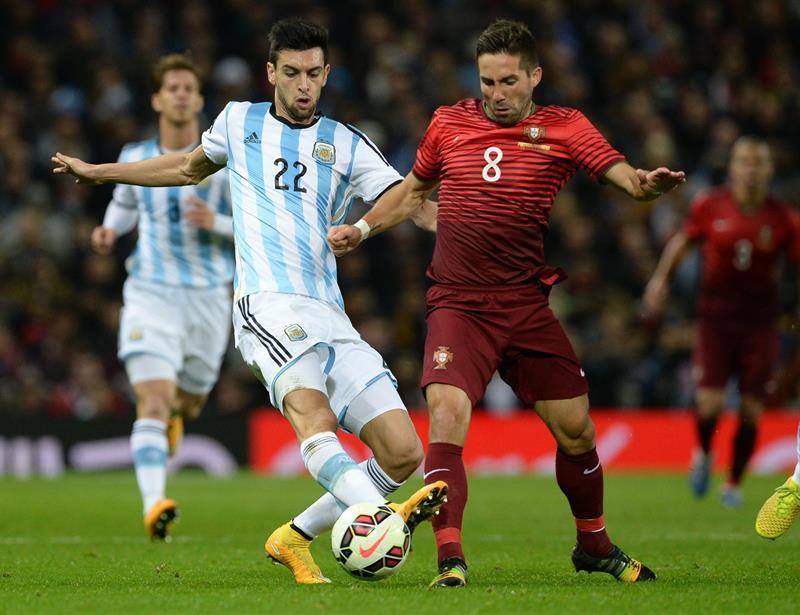El jugador de Portugal Joao Moutinho (d) disputa un balón con Javier Pastore (i) Argentina. Foto: EFE