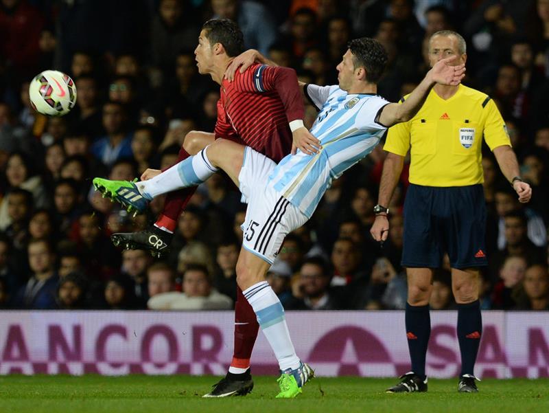 El jugador de Portugal Cristiano Ronaldo (d) disputa un balón con Martin Demichelis (d) Argentina. Foto: EFE